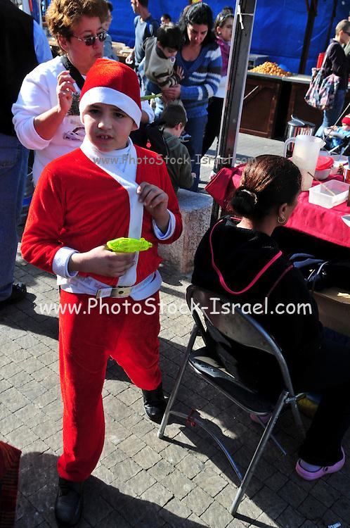 Israel, Haifa, Wadi Nisnas, Children dressed up as Santa Claus in a parade during the Holiday of holidays festival, celebrating Hanuka-Christmas-Ramadan December 2009