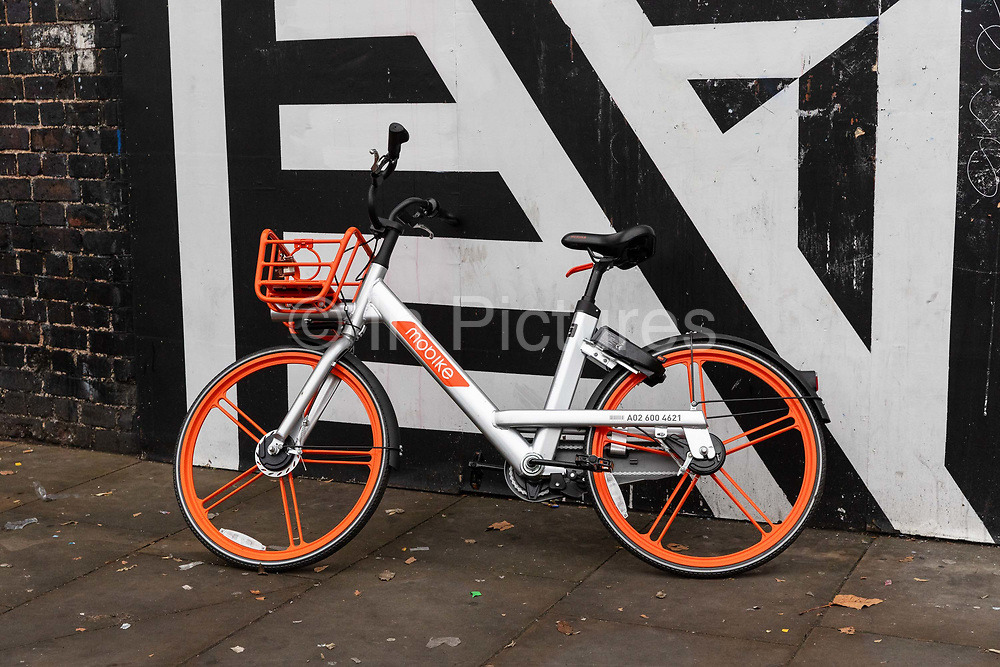 A Mobike dockless sharing bicycle left on the street in east London, England on November 23, 2018 . The increasing use of dockless sharing bikes in London comes after two Chinese companies, Ofo and Mobike, launched their mobile app-based service in the capital last year.