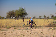 Young Indian Bishnoi boy in school uniform riding bicycle to her school near Rohet in Rajasthan, Northern India