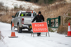 © Licensed to London News Pictures. 08/02/2021. Surrey, UK. A ranger closes the roads to Box Hill as treacherous conditions continue as Storm Darcy hits the South East again with more yet snow and freezing temperatures. The Met Office have issue numerous weather warnings for heavy snow and ice with disruption to travel, power cuts and possible stranded vehicles as the bad weather continues.  Photo credit: Alex Lentati/LNP