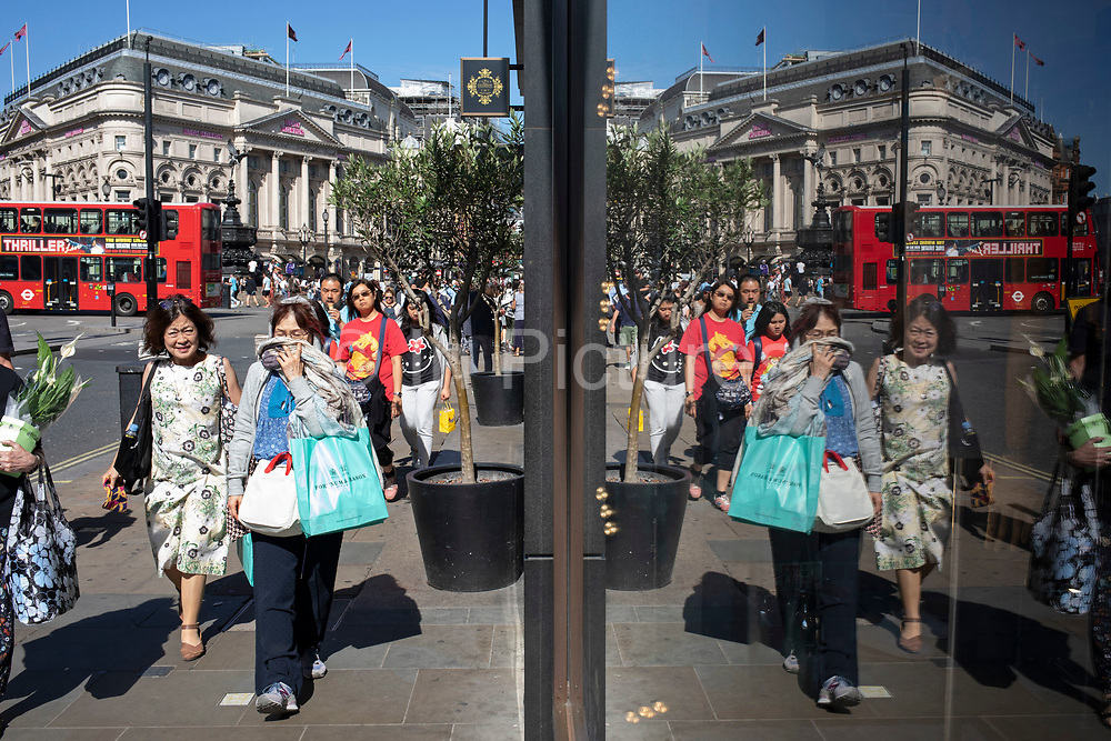 Passers by create a symmetrical reflection in a shop window along Piccadilly in London, United Kingdom.