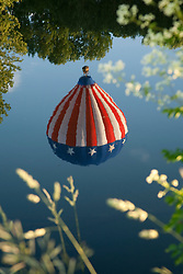 North America, United States, Vermont, Queechee, Queechee Hot Air Balloon festival, held in June.  Reflection of American Flag balloon in Ottaqueechee River.
