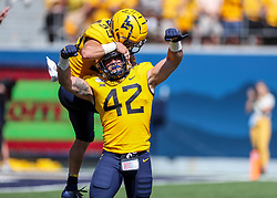 Sep 14, 2019; Morgantown, WV, USA; West Virginia Mountaineers tight end Logan Thimons (42) celebrates after blocking a punt from North Carolina State Wolfpack punter Trenton Gill (97) during the third quarter at Mountaineer Field at Milan Puskar Stadium. Mandatory Credit: Ben Queen-USA TODAY Sports