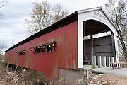 """Neet Covered Bridge (126 feet long), built in 1904 by J.J. Daniels over Little Raccoon Creek, on Bridgeton Road, Parke County, Indiana, USA. Red and white paint protects the wood. The traditional """"Cross this bridge at a walk"""" sign required slow vehicle speed, but auto traffic is now diverted to an adjacent crossing."""