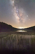 The milky way streams above Summit Lake of the Cranberry Wilderness in West Virginia, stars reflecting in the waters between blades of grass and lily pads.