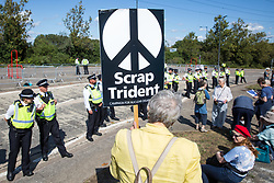 London, UK. 4 September, 2019. Metropolitan Police officers form a cordon around anti-nuclear activists protesting outside ExCel London on the third day of a week-long carnival of resistance against DSEI, the world's largest arms fair. The third day's protests were organised by the Campaign for Nuclear Disarmament (CND) and Trident Ploughshares.
