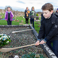 Dara McCarthy from Newmarket-on-Fergus lays a hurley on the grave of Jim Guerin
