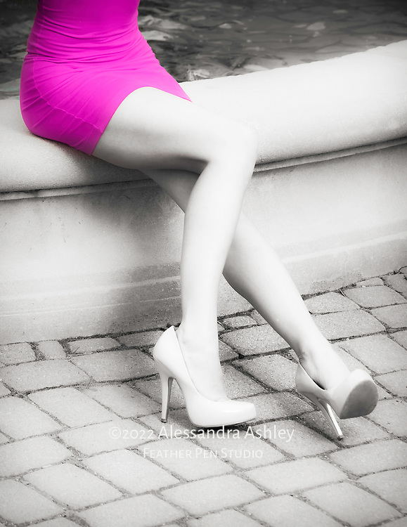 Young woman in pink dress and high heels at edge of urban fountain.