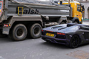 Lamborghini supercar with purple trim pulls up beside a contruction transport truck showing a difference in scale and stature on 5th March 2021 in London, England, United Kingdom.