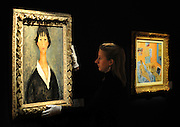 © Licensed to London News Pictures. 02/02/2012, London, UK. A  assistant hangs 'Jeune file aux cheveux noirs' by the italian artist Amedeo Modigliani. The painting is expected to fetch 700,000-1,000,000GBP. Photo call at Bonhams, London for Impressionist and Modern Art Auction preview. Photo credit : Stephen Simpson/LNP