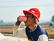 10 FEBRUARY 2016 - BAN LAEM, PHETCHABURI, THAILAND:  A salt field worker takes a drink of water during the salt harvest in Phetchaburi province, Thailand. The salt harvest in Thailand usually starts in February and continues through May. Salt is harvested in many of the provinces along the coast, but the salt fields in Phetchaburi province are considered the most productive. The salt fields are flooded with sea water, which evaporates off leaving salt behind. Salt production relies on dry weather and producers are hoping the current drought will mean a longer harvest season for them.     PHOTO BY JACK KURTZ
