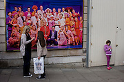 Older woman and younger girls in front of poster for Mamma Mia musical in London's West End.