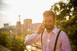 Businessman talking on mobile phone at sunset, Munich, Bavaria, Germany