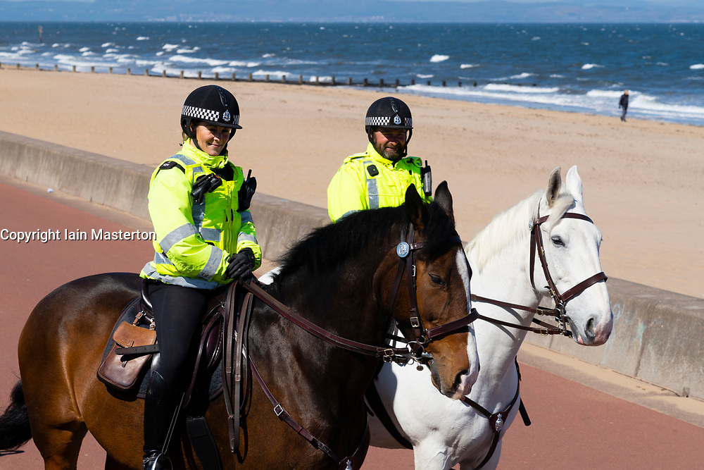Portobello beach and promenade near Edinburgh during Coronavirus lockdown on 19 April 2020. Empty beach with single yellow bench. Mounted police patrol the promenade.