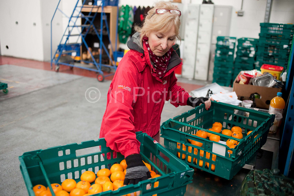 Woman selecting oranges, Fareshare is a small charity in London that uses food from supermarkets that would otherwsie be wasted, and distributes it to those in need, working in collaboration with food banks and community groups in London.