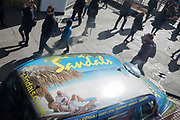 Passers-by and the roof of a black London cab carrying an ad for Sandals Caribbean beach holidays, on 25th March 2019, in London, England.