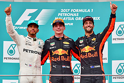 SEPANG, Oct. 1, 2017  Red Bull driver Max Verstappen (C) of the Netherlands, Mercedes driver Lewis Hamilton (L) of Britain and Red Bull driver Daniel Ricciardo of Australia pose for pictures on the podium after the Formula One Malaysia Grand Prix at the Sepang Circuit in Malaysia, on Oct. 1, 2017. Max Verstappen claimed the title of the event. (Credit Image: © Chong Voon Chung/Xinhua via ZUMA Wire)
