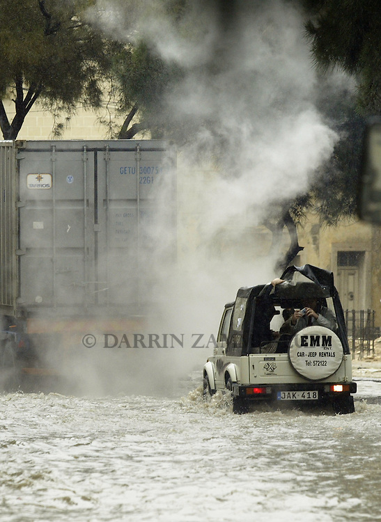 Steam rises from the exhaust of a truck as it makes its way through flood waters in the town of Msida, outside Valletta, November 6, 2002.  Heavy rainfall caused widespread flooding and damage throughout the Maltese islands, though no serious injuries were reported...MALTA OUT..REUTERS/Darrin Zammit Lupi