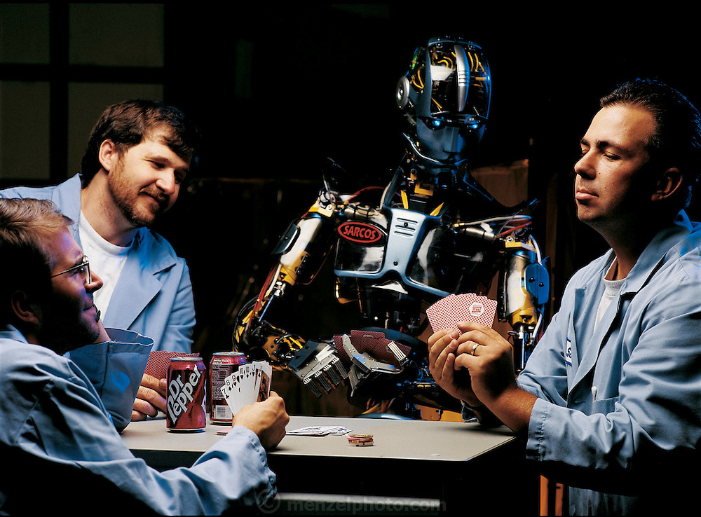 In a photo-illustration, SARCOS, an animatronic robot built by the SARCOS Research Corp., a Salt Lake City, UT, robotics company, appears to peer at the seven-card-stud hand of Scott Reynolds (at right), one of the engineers responsible for creating him (with technicians Doren Prue, center, and Charles Ledger). From the book Robo sapiens: Evolution of a New Species, page 218-219.