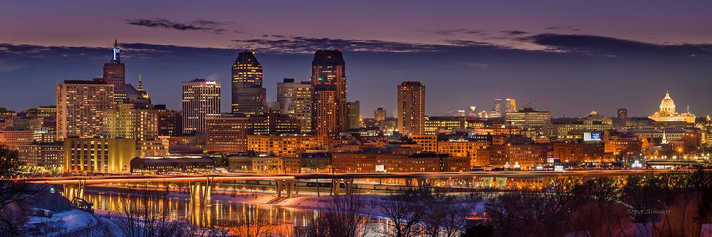 """Downtown St. Paul gives off a beautiful glow. This view from Mounds Park is the only place where you can see the downtowns of St. Paul and Minneapolis in the same frame. And one of the rare occasions when Minneapolis takes a back seat to St. Paul! The First Bank """"1"""" is ice blue this week to recognize the state high school hockey tournaments occurring in St. Paul. This panorama is a composite of six photos."""