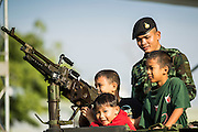 """11 JANUARY 2014 - BANGKOK, THAILAND: Thai children and a Thai soldier stand behind a machine gun on top of a vehicle during Children's Day in Bangkok. The Royal Thai Army hosted a """"Children's Day"""" event at the 2nd Cavalry King's Guard Division base in Bangkok. Children had an opportunity to look at military weapons, climb around on tanks, artillery pieces and helicopters and look at battlefield medical facilities. The Children's Day fair comes amidst political strife and concerns of a possible coup in Thailand. Earlier in the week, the Thai army announced that movements of armored vehicles through Bangkok were not in preparation of a coup, but were moving equipment into position for Children's Day.      PHOTO BY JACK KURTZ"""