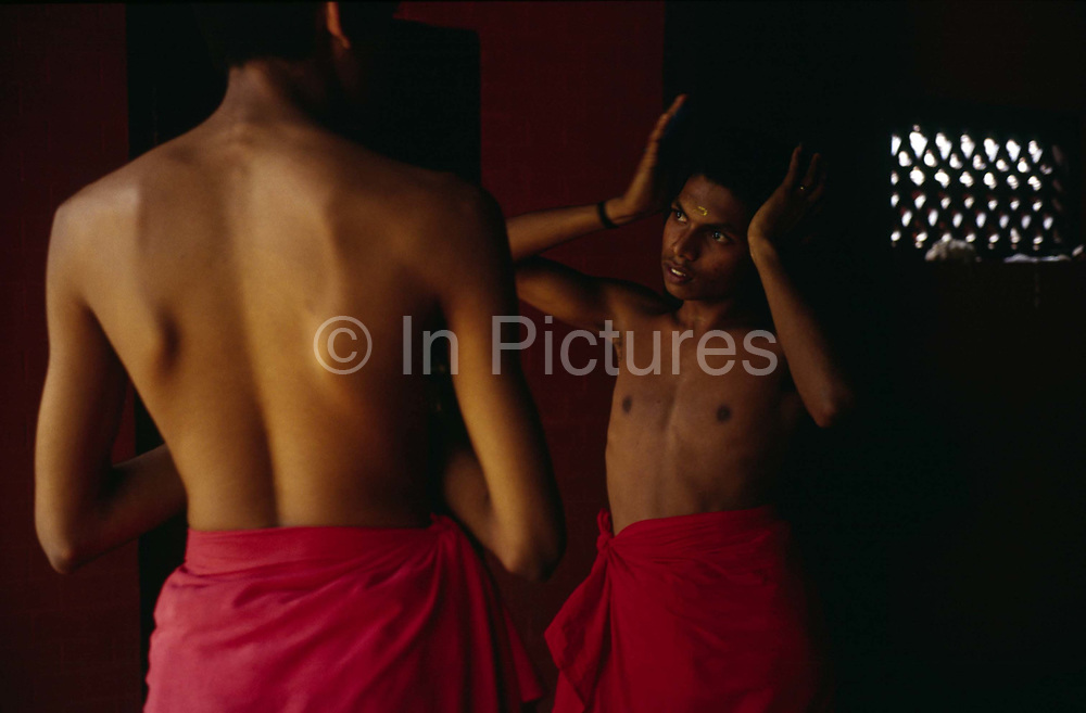 Two students, one combing his hair at the Kerala Kalamandalam<br /> The Kalamandalam was founded in 1930 to preserve the cultural traditions of Kathakali, the stylised dance drama of Kerala. Kathakali is the classical dance-drama of Kerala, South India, which dates from the 17th century and is rooted in Hindu mythology. Kathakali is a unique combination of literature, music, painting, acting and dance performed by actors wearing extensive make up and elaborate costume who perform plays which retell in dance form stories from the Hindu epics.