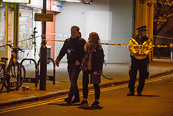 © Licensed to London News Pictures.24/11/2020. London, UK. Police officers guard crime scene in Hoxton Street Market, east London, following a firearm discharge at around 2:20pm today - no reports of any injuries at the scene. London Photo credit: Marcin Nowak/LNP