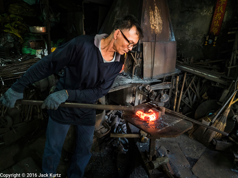 25 JANUARY 2016 - BANGKOK, THAILAND: The man who operates a small one person workshop making heavy chains for boat anchors bends the heated steel into shape. The metal for the chains is heated until it glows red and then it's pounded into shape. The Talat Noi neighborhood in Bangkok started as a blacksmith's quarter. As cars and buses replaced horse and buggy, the blacksmiths became mechanics and now the area is lined with car mechanics' and blacksmiths' shops.          PHOTO BY JACK KURTZ