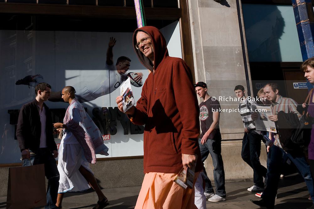 A diving England rugby player spreads across the Nike shop window at Oxford Circus, in front of Hare Krishna devotees.