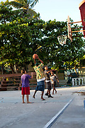 Boys younf men playing basketball, Caye Caulker island, Belize.