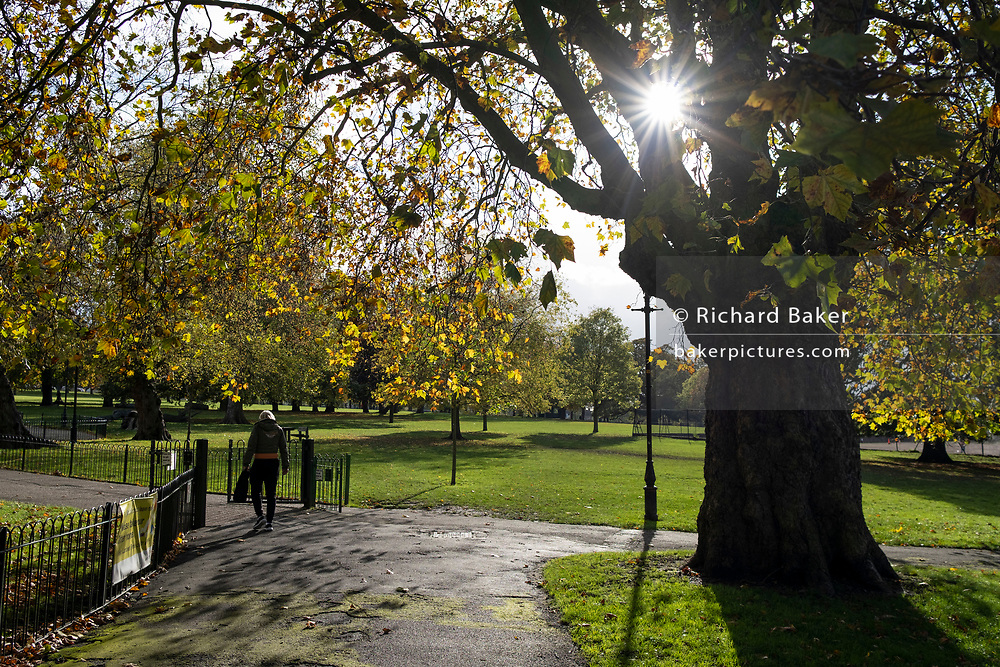 A solitary man walks through afternoon Autumnal sunlight in Ruskin Park, a popular green space in south London, on 26th October 2020, in London, England.