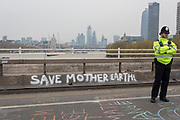 A police officer and Climate Change graffiti from Extinction Rebellion campaign for a better future for planet Earth after blocking Waterloo Bridge and as part of a multi-location 5-day Easter protest around the capital, on 16th April 2019, in London, England.