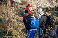 LESVOS, GREECE - FEBRUARY 09: Refugees climb up a small hill after disembarking from their boat in a beach on February 09, 2016 in Lesvos, Greece. Photo: © Omar Havana. All Rights Are Reserved