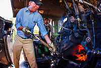 Governor John Hickenlooper (of Colorado) acts as the train fireman adding coal, stoking the boiler on the steam locomotive on a visit aboard the the Cumbres & Toltec Scenic Railroad, from Antonito to Osier, Colorado during peak autumn color. The Cumbres & Toltec Scenic Railroad has been jointly owned by the States of Colorado and New Mexico since 1970 when it was purchased from the Denver and Rio Grande Western Railway, which was going to scrap the line. The train makes a 64 mile run between Antonito, Colorado and Chama, New Mexico. The railroad is the highest and longest narrow gauge steam railroad in the United States with a track length of 64 miles. The train traverses the border between Colorado and New Mexico, crossing back and forth between the two states 11 times. The narrow gauge track is 3 feet wide. It runs over 10,015 ft (3,053 m) Cumbres Pass.