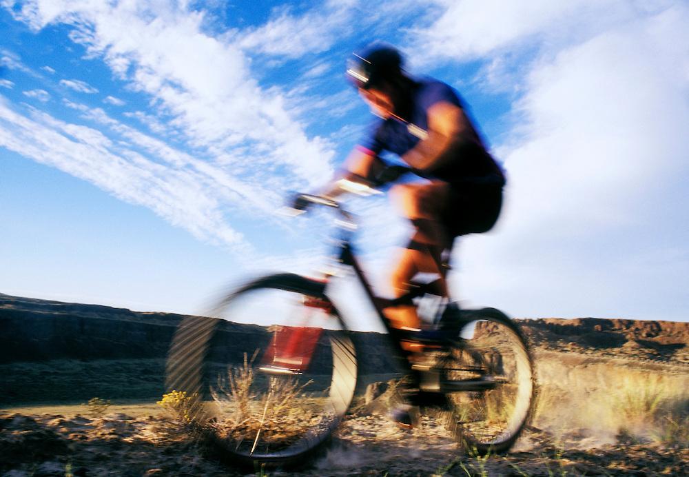 Blur shot of a man riding a mountain bike in Frenchmans Coulee near Vantage, Washington, USA