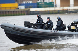 © London News Pictures. 04/05/2012. London, UK. A police boat escorting Royal Navy helicopter carrier HMS Ocean towards Greenwich for an Olympics security exercise as part of operation Olympic Guardian on May 4, 2012. The ship will be berthed at Greenwich throughout the Olympics, acting as logistic hub and helicopter launch platform. Photo credit: Ben Cawthra/LNP