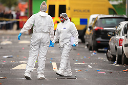 Forensics officers at the scene in Claremont Road, Moss Side, Manchester, where several people have been injured after a shooting.