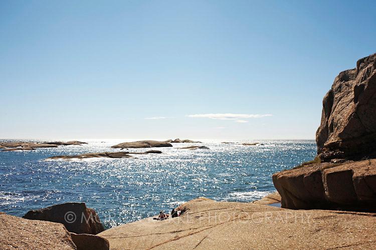 Rakke, Norway. Person sun bathing on rock by sea