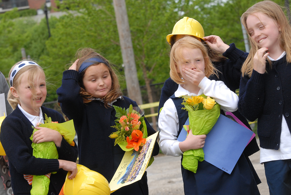 Students react after a strong breeze stole one of their ceremonial plastic hard hats while attending a ground breaking ceremony at Old St. Mary's Catholic School in Chicago's South Loop neighborhood.