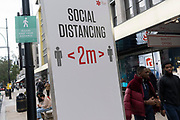 Londoners pass beneath a social distancing sign that urges the public to keep 2 metres apart on Oxford Street during the second (Autumn) wave of the Coronavirus pandemic, on 8th October, 2020, in London, England.