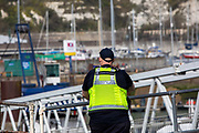 An immigration enforcement officer watches as asylum seekers arrive into Dover docks on board a Boarder Force RIB boat after they were rescued in the English Channel while crossing on the 31st of March 2021 in Dover, Kent, United Kingdom. About 30 men and women arrived today on two small boats they were taken off the boat by UK Boarder Force and taken into a processing centre on the dock side.