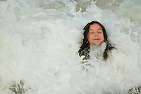 Young girl age 10, playing in the ocean waves at the beach.