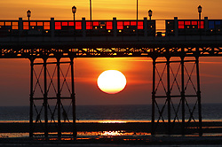 © Licensed to London News Pictures. 10/10/2018. Worthing, UK.  The sun rises behind Worthing pier on a day - when unseasonably high temperatures expected in parts of the UK.Photo credit: Peter Macdiarmid/LNP
