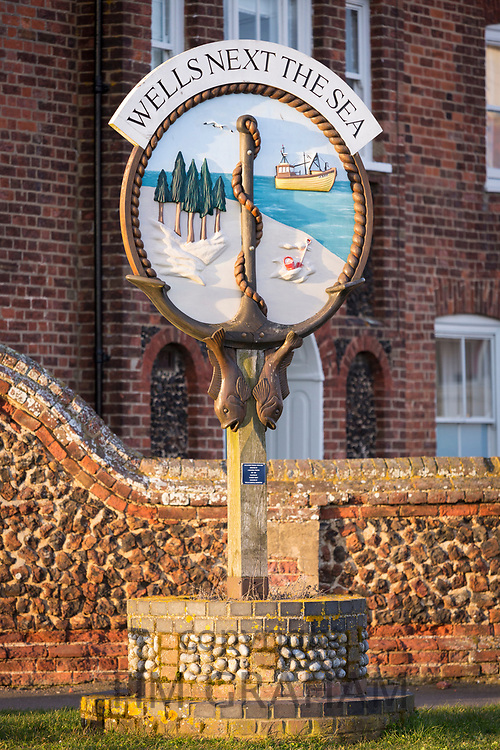 Wells Next The Sea - one of the traditional painted village signs by traditional brick and flint wall in North Norfolk, UK