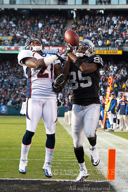 Nov 6, 2011; Oakland, CA, USA; Denver Broncos cornerback Andre' Goodman (21) breaks up a pass intended for Oakland Raiders wide receiver Darrius Heyward-Bey (85) during the third period at O.co Coliseum. Denver defeated Oakland 38-24. Mandatory Credit: Jason O. Watson-US PRESSWIRE