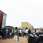 Electronic waste export to Nigeria...Alaba International Market, one of the largest markets for electronic goods in West Africa.  New and old - and a lot of non-working electronic goods such as TVs and computers come in to the market via Lagos harbour from the US, Western Europe and China...Container 4629416 from the UK is being emptied for its load, including the TV tracked by Greenpeace.  Rows of second hand tvs from the container, lost made by Philips..The shipment - TV-set originally delivered to municipality-run collecting point in UK for discarded electronic products - was tracked and monitored by Greenpeace using a combination of GPS (Global Positioning System using satellites), GSM (positioning using data from mobile networks to triangulate approximate positions) and an onboard radiofrequency transmitter (used for making triangulations in combination with handheld directional receivers used by team on ground) is placed inside the TV-set.  The TV arrived in Lagos in container no 4629416.