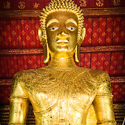 The bust of the large Buddha statue at Wat Mai Suwannaphumaham.  Wat Mai, as it is often known, is a Buddhist temple in Luang Prabang, Laos, located near the Royal Palace Museum. It was built in the 18th century and is one of the most richly decorated Wats in Luang Prabang.
