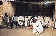 Husa men take early morning tea. Behind them are posters of America's most wanted, including Osama Bin Laden..The implementation of Islamic Sharia Law across the twelve northern states of Nigeria, centres upon Kano, the largest Muslim Husa city, under the feudal, political and economic rule of the Emir of Kano. Islamic Sharia Law is enforced by official state apparatus including military and police, Islamic schools and education, plus various volunteer Militia groups supported financially and politically by the Emir and other business and political bodies. Fanatical Islamic Sharia religious traditions  are enforced by the Hispah Sharia police. Deliquancy is controlled by the Vigilantes volunteer Militia. Activities such as Animist Pagan Voodoo ceremonies, playing music, drinking and gambling, normally outlawed under Sharia law exist as many parts of the rural and urban areas are controlled by local Mafia, ghetto gangs and rural hunters. The fight for control is never ending between the Emir, government forces, the Mafia and independent militias and gangs. This is fueled by rising petrol costs, and that 70% of the population live below the poverty line. Kano, Kano State, Northern Nigeria, Africa