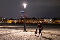 © Licensed to London News Pictures. 10/02/2021. London, UK. A woman runs with her dog on a snowy Blackheath Common in South East London. Snow is expected for large parts of the UK and a yellow weather warning is in place across the east of England as Storm Darcy hits the UK. Photo credit: George Cracknell Wright/LNP