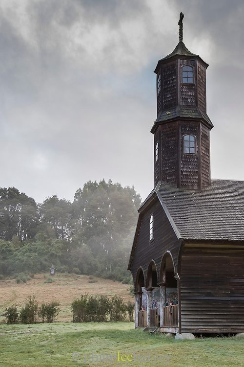 Tower of Church of Vilupulli and trees, Chiloe Island, Chile